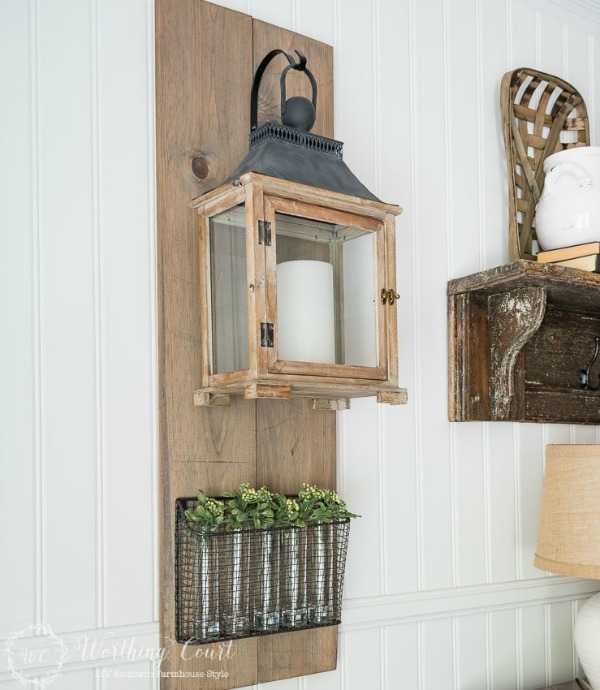 Battery-operated-candle-in-a-hanging-lantern-on-a-diy-wood-plaque-and-glass-vases-filled-with-greenery-sprigs