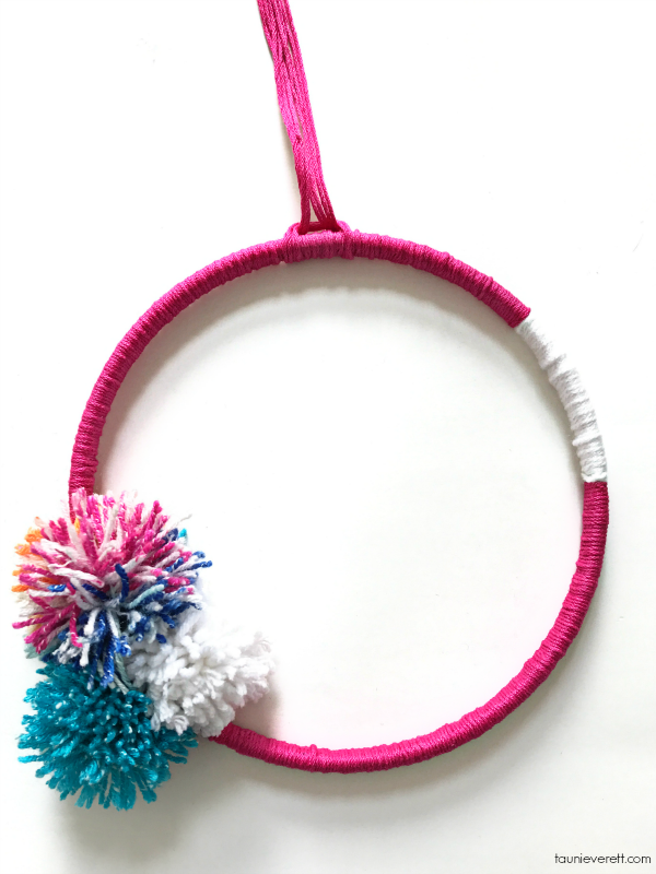 Modern embroidery hoop wreath with pom poms. Easy project under 30 min. hands on crafting. #wreath #modernwreath #yarnwreath #pompomwreath