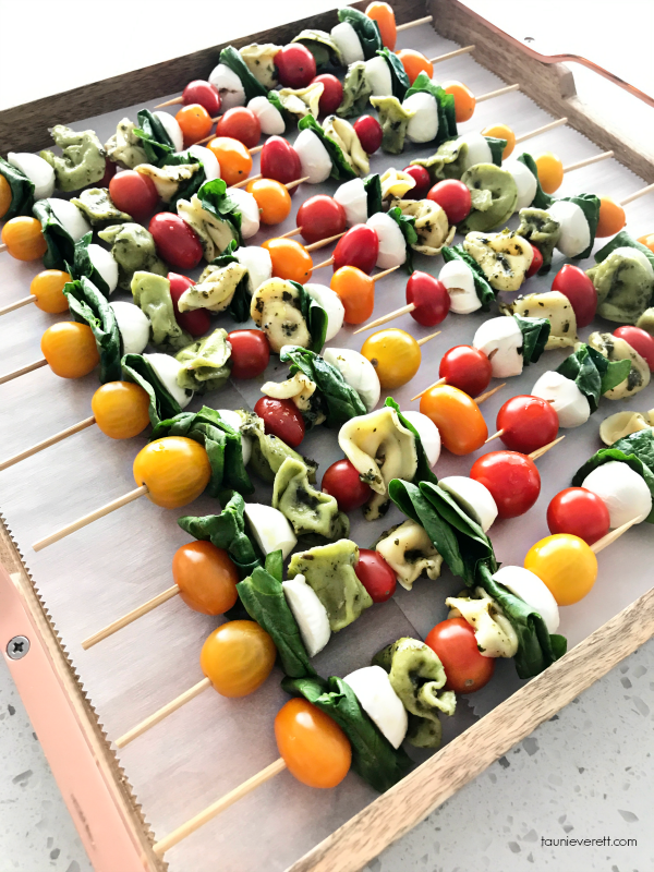 Easy to assemble pesto tortellini skewers. These tortellini skewers make for a great party appetizer or can be served over a salad for dinner. Perfect for summer entertaining. #pesto #tortellini #appetizer #recipe